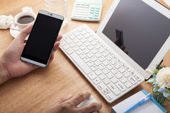 Hands using cell phone and laptop on desk wood and Business work. Place, business objects Royalty Free Stock Photo