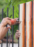 Hands using electric drill on fence wood Stock Image