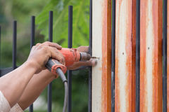 Hands using electric drill on fence wood Royalty Free Stock Images
