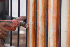 Hands using electric drill on fence wood Royalty Free Stock Photos
