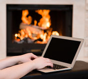 Hands using laptop against the background of the fireplace Stock Photography