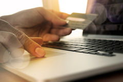 Hands using laptop and holding credit card with social media Stock Photos