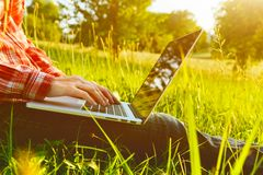 Hands using laptop typing. Hands using laptop and typing in summer grass Stock Images