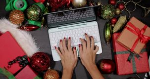 Hands using laptop between Xmas decorations. Top view of unidentified woman hands using a laptop computer between Xmas decorations and gift boxes on the table stock video