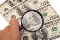 Hands using a magnifying glass to see US dollar bill Royalty Free Stock Images