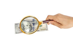 Hands using a magnifying glass to see US dollar bill Stock Images