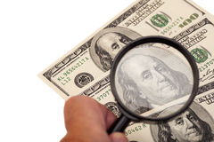 Hands using a magnifying glass to see US dollar bill Royalty Free Stock Photo