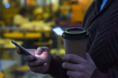 Hands using a phone texting on smartphone app and holding paper cup of coffee. Stock Image