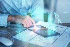 Investment, economy, technology and media concept. Hands using tablet with abstract forex chart at modern office desk. Investment, economy, technology and media Stock Image