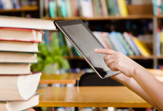 Hands using tablet computer in library.  Stock Photo