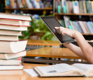 Hands using tablet computer in library Stock Image