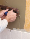 Hands using trowel. To spread mortar for ceramic tile installation Royalty Free Stock Image
