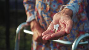 Hands of very old woman taking pills, close up of an elderly woman hand her medication, health issues at an old age