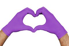 Hands in violet medical gloves showing heart sign isolated on white background stock photo