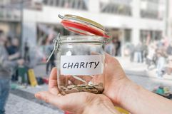 Hands of volunteer holds jar with coins. Collecting money for charity Royalty Free Stock Image