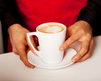 Hands of waiter serving a cup of cappucino Stock Images