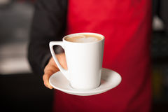 Hands of waiter serving a cup of cappucino Royalty Free Stock Image