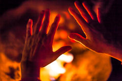 Hands on fire. Close-up of a night scene of hands get warm by the fire. Concept of poverty, human warmth, camping, bbq, barbeque,  braai grill Stock Images
