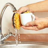 Hands wash the coffee cup under running water in kitchen Stock Images