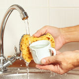 Hands wash the cup under running water in kitchen Royalty Free Stock Photo