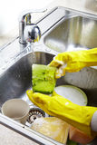 Hands washing dishes with running water from faucet Royalty Free Stock Photos