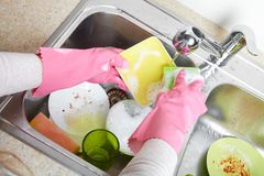 Hands washing dishes with running water from faucet. In sink Stock Photography