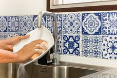 Hands washing white plate in kitchen sink with running water. With blue tile royalty free stock photo