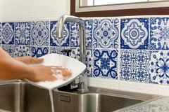 Hands washing white plate in kitchen sink with running water. With blue tile stock photo