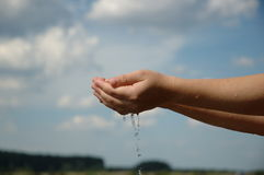 Hands in water 3. Hands splashing water against blue sky Royalty Free Stock Photo