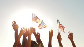 Hands waving US flags. Small flags on sun background. Pride and joy. Happy to live in America stock video