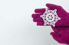 Hands wearing pink gloves holding a big snowflake. Royalty Free Stock Photos