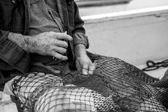 Hands of weathered fisherman mending net. Weathered fisherman mending his net, focus on hands Stock Photography