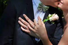 The Hands of the Wedding Couple. Are placed in the centre of the image and it is only possible to get a small hint of a kiss up at the right corner Stock Photography