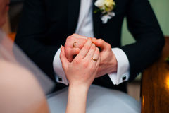 Hands of wedding couple putting golden rings to finger of each other. royalty free stock photos