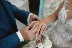 Hands of wedding couple putting golden rings to finger of each other. Royalty Free Stock Image