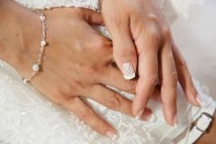 Hands on the wedding dress with white nails manicures Stock Image