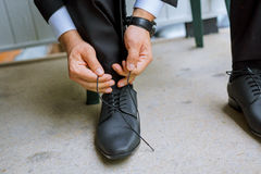 Hands of wedding groom getting ready suit. Hands of wedding groom getting ready in suit putting his wedding shoes Stock Photography