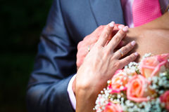 Hands with wedding ring on brides shoulder Stock Photos