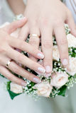Hands with wedding rings. Wedding bouquet from pastel pink roses, hands and rings royalty free stock photos