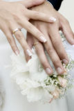 Hands with wedding rings. Wedding bouquet from white and pastel pink flowers, hands and rings royalty free stock image
