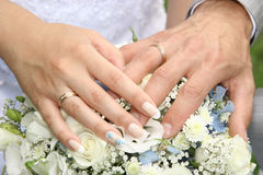 Hands with wedding rings. 2 hands with wedding rings lay on a wedding bouquet Stock Images