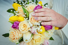 Hands with wedding rings and bouquet Stock Photos