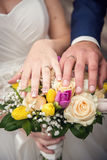 Hands with wedding rings and bouquet. From roses Royalty Free Stock Images