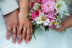 Hands with wedding rings and bouquet. From roses Royalty Free Stock Photography