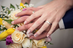 Hands with wedding rings and bouquet. From roses Royalty Free Stock Image
