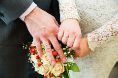 Hands with wedding rings on bridal bouquet Stock Image