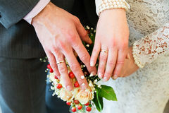 Hands with wedding rings on bridal bouquet Royalty Free Stock Image