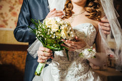 Hands with wedding rings on bridal bouquet of Stock Photography