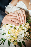 Hands with wedding rings on bridal bouquet of Royalty Free Stock Photos