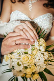 Hands with wedding rings on bridal bouquet of Stock Image